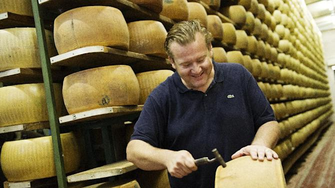 "This book cover image released by Ballantine Books shows Michael White with a wheel of cheese to be used for a dish from his book ""Classico E Moderno: Essential Italian Cooking,"" with Andrew Friedman. White is the chef and owner of Marea restaurant in New York. (AP Photo/Ballantine Books, Evan Sung)"