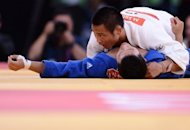 Japan&#39;s Masashi Ebinuma (white) competes with Korea&#39;s Cho Jun-Ho (blue) during the under-66kg quarter-final match at the ExCel arena in London. The Olympic judo quarter-final between world champion Masashi Ebinuma and Cho Jun-Ho of South Korea descended into farce on Sunday after Cho was awarded victory only for his Japanese rival to be declared the winner moments later