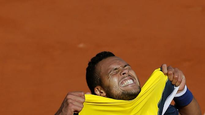 France's Jo-Wilfried Tsonga puts his shirt on his face after defeating Switzerland's Roger Federer during their quarterfinal match of the French Open tennis tournament at the Roland Garros stadium Tuesday, June 4, 2013 in Paris. Tsonga won 7-5, 6-3, 6-3. (AP Photo/Michel Spingler)