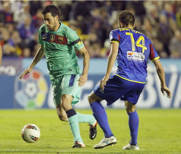 Barcelona's Busquets and Levante's Torres fight for the ball during their Spanish first division soccer match in Valencia