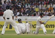 Indian cricket captain and wicket keeper Mahendra Singh Dhoni stumbles as New Zealand cricketer Kruger Van Wyk plays a shot. India won the opening Test by an innings and 115 runs in Hyderabad