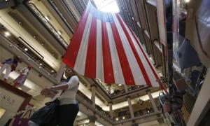 Shopper walks past a giant U.S. flag on display, ahead of the Memorial Day holiday, in a department store in Chicago