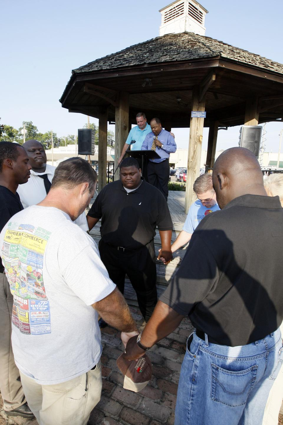 Crystal Springs, Miss., civic and religious leaders gather at the town square for a prayer rally in support of racial reconciliation Monday, July 30, 2012 following the actions of some congregants at the First Baptist Church which prevented a black couple from getting married there. (AP Photo/Rogelio V. Solis)