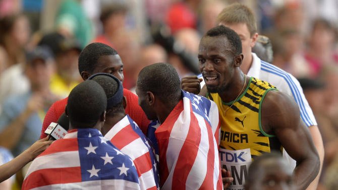 Jamaica's Usain Bolt, right, speaks to a U.S. relay member as they are interviewed by a television broadcaster following the men's 4x100-meter relay final at the World Athletics Championships in the Luzhniki stadium in Moscow, Russia, Sunday, Aug. 18, 2013. (AP Photo/Martin Meissner)