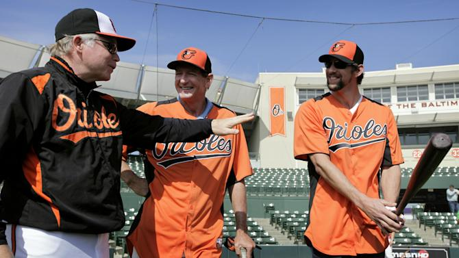 Baltimore Orioles manager Buck Showalter, left, talks with golf coach Hank Haney, center, and former Olympic swimmer Michael Phelps during a Baltimore Orioles baseball spring training workout Thursday, Feb. 21, 2013, in Sarasota, Fla.  Phelps, a native of Baltimore who was in the area filming his Golf Channel show The Haney Project, took batting practice with the team. (AP Photo/Charlie Neibergall)