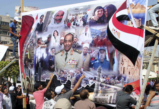 Egyptians hang a banner supporting Field Marshal Mohamed Hussein Tantawi, head of Egypt's ruling military council, at center, during a pro military council rally in Cairo, Egypt, Friday July 15, 2011. (AP Photo)