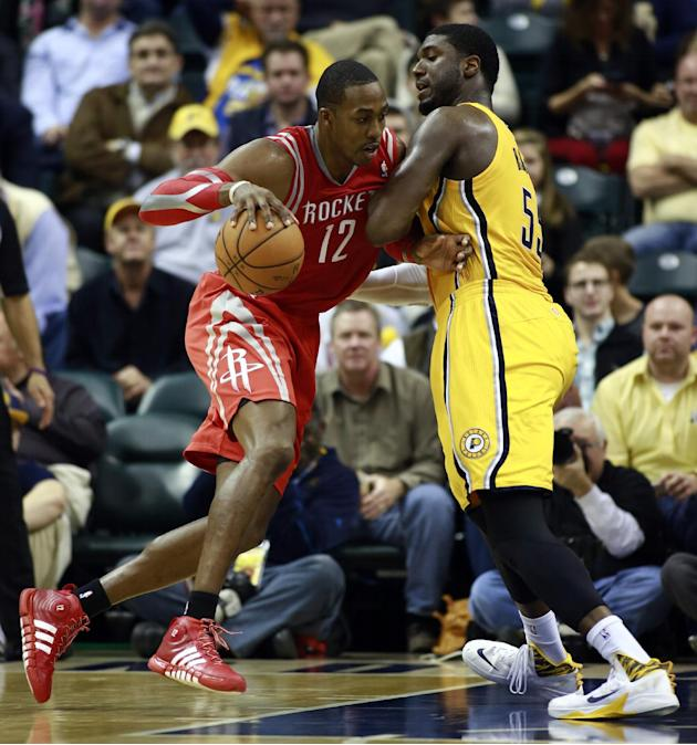 Houston Rockets center Dwight Howard (12) moves toward the basket whi2le guarded by Indiana Pacers center Roy Hibbert in the second half of an NBA basketball game in Indianapolis, Friday, Dec. 20, 201