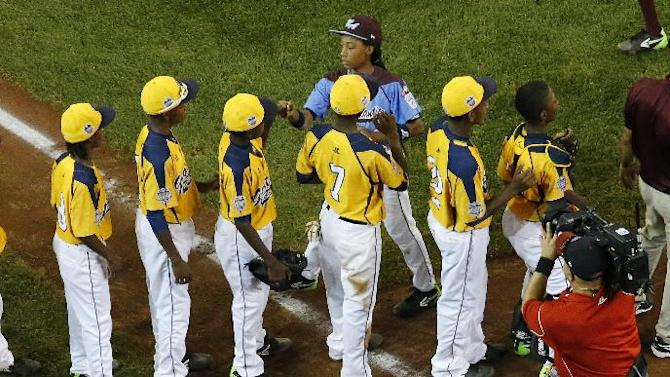 Philadelphia's Mo'ne Davis, top center, shakes hands with the players from the Chicago team after Philadelphia lost 6-5 in an elimination baseball game at the Little League World Series tournament in South Williamsport, Pa., Thursday, Aug. 21, 2014. (AP Photo/Gene J. Puskar)