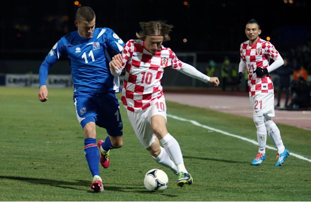 Croatia's Luka Modric is challenged by Iceland's Alfred Finnbogason, left, during their World Cup qualifying playoff first leg soccer match in Reykjavik, Iceland, Friday Nov. 15, 2013