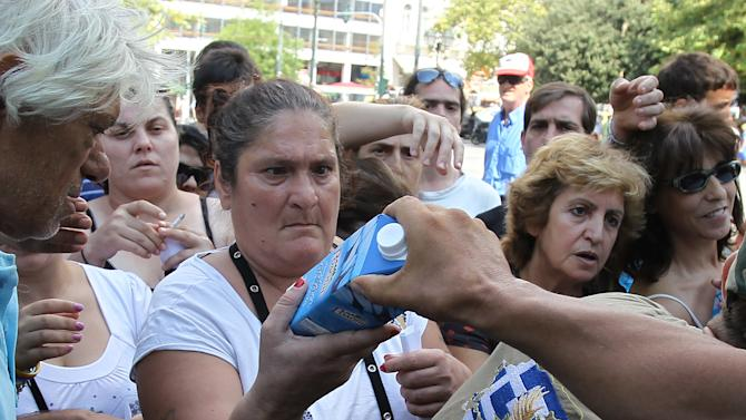 Members of Greece's extreme right Golden Dawn party hand out milk at Athens' main Syntagma Square, opposite parliament, on Wednesday, Aug. 1, 2012. The volunteers checked ID cards of the public before handing Greek citizens food that included milk cartons, pasta, potatoes and olive oil. Golden Dawn won 18 seats in the 300-seat parliament in June general elections. Senior party members openly support a policy of granting Greek citizenship based on racial identity. The party has stepped up its charity effort as Greece is suffering through a fifth year of recession, with rapidly rising rates of poverty and unemployment. (AP Photo/Thanassis Stavrakis)