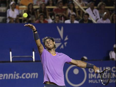 Nadal of Spain serves to compatriot Almagro during men's singles match at Acapulco International tennis tournament in Acapulco