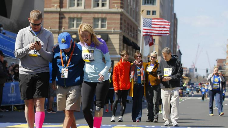 2013 Boston Marathon bombing survivor Haslet-Davis crosses the marathon finish line with her husband Davis during a Tribute Run for survivors and first responders in Boston