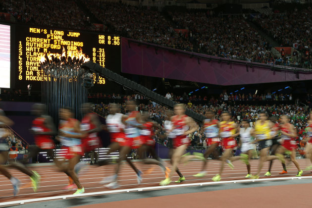 Runners pass by the Olympic flame during the men's 10,000-meter final during athletics competition in the Olympic Stadium at the 2012 Summer Olympics, Saturday, Aug. 4, 2012, in London. (AP Photo/Matt Dunham)