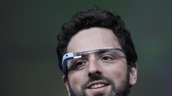 Google co-founder Sergey Brin demonstrates Google's new Glass, wearable internet glasses, at the Google I/O conference in San Francisco, Wednesday, June 27, 2012.  The audience got live video feeds from their glasses as they descended to land on the roof of the Moscone Center, the location of the conference. (AP Photo/Paul Sakuma)