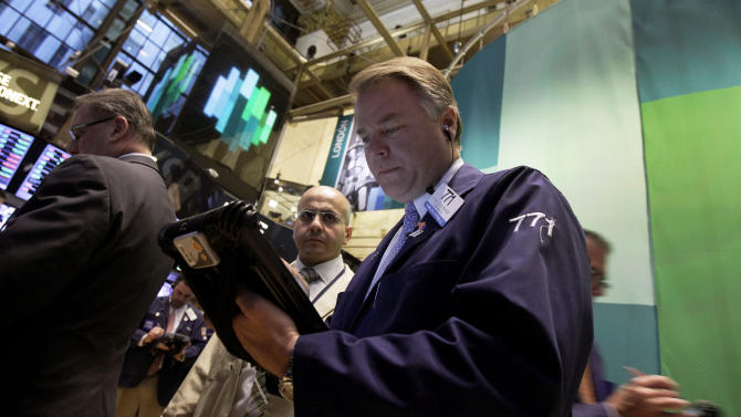 Trader F. Hill Creekmore, center, works on the floor of the New York Stock Exchange Monday, Oct. 22, 2012. A weak forecast from heavy equipment maker Caterpillar and other poor earnings results weighed on the U.S. stock market in early trading. (AP Photo/Richard Drew)