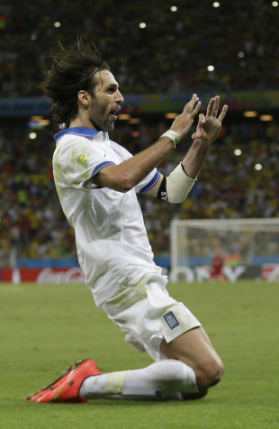 Greece's Giorgos Samaras celebrates scoring his side's second goal during the group C World Cup soccer match between Greece and Ivory Coast at the Are...