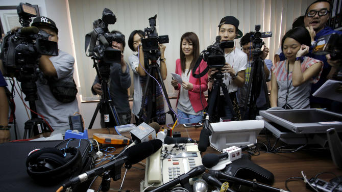 Reporters crowd around a speakerphone as they listen to a transgender woman on it after she won a legal ruling at Hong Kong's top court allowing her to marry, in Hong Kong Monday, May, 13, 2013. Hong Kong's top court granted the transgender woman, identified only as W, the right to marry her boyfriend Monday in a watershed ruling that falls short of allowing same-sex marriage. The surprise decision only covers the right of a transgender person who was born male to marry a man, and for one who was born female to marry a woman. (AP Photo/Vincent Yu)