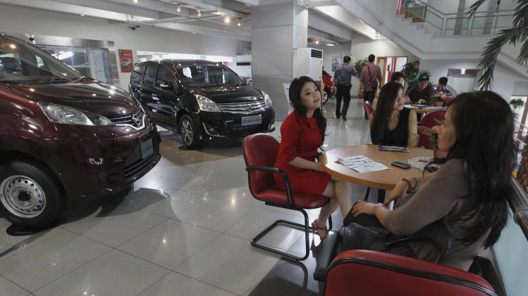 A saleswoman talks to customers at a Nissan dealership in Jakarta