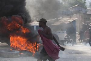 A protester walks by burning tires placed by demonstrators…