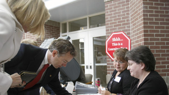 Kentucky Republican Senate candidate Rand Paul signs the election register in front of poll workers Vicky Finn, right, and Anita Bishop, as he prepares to vote in Bowling Green, Ky., Tuesday, Nov. 2, 2010. Paul's wife Kelley is at left. (AP Photo/Ed Reinke)
