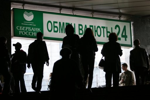 <p>File photo shows people walking past a currency exchange sign at Sberbank, one of Russia's largest banks, in Moscow. Russia's central bank on Monday announced plans to go ahead with the long-delayed auction a 7.58-percent stake in main lender Sberbank following a recent improvement in global market sentiment.</p>