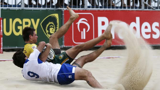 Bicudo of Brazil is tackled by Pratti of Italy during their men's Beach Rugby International tournament match at Ipanema beach in Rio de Janeiro