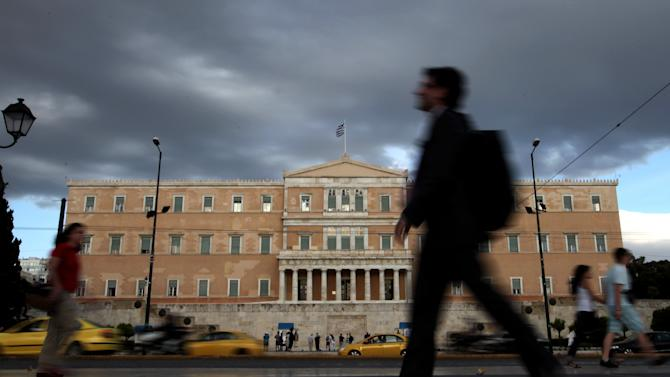 People walk outside the Greek parliament on Tuesday, May 15, 2012. Greece is headed for another month of political paralysis ahead of new elections in mid-June, after party leaders on Tuesday failed to reach an agreement to build a coalition government.  The protracted deadlock and the prospect of an anti-austerity party winning the new vote hammered Europe's markets on fears that the debt-crippled country could be forced out of the European single currency, triggering shock-waves throughout the 17-country eurozone. (AP Photo/Petros Giannakouris)