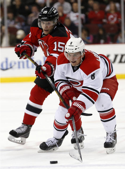 New Jersey Devils' Tuomo Ruutu, of Finland, and Carolina Hurricanes' Andrei Loktionov, of Russia, compete for the puck during the first period of an NHL hockey game, Saturday, March 8, 2014, i