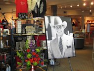 "A large portrait of Larry Hagman can be seen by a bouquet of flowers at the entrance of the gift shop at Southfork Ranch on Saturday, Nov. 24, 2012, in Parker, Texas. Officials at the ranch, the setting for the TV series ""Dallas"" where Hagman played the infamous J.R. Ewing, placed the photo there in memory of Hagman, who died Friday, Nov. 23, 2012 in Dallas. He was 81. (AP Photo/Angela K. Brown)"