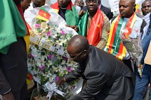 A man lays flowers in tribute to victims of Boko Haram …
