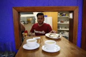 "A Venezuelan man works at the kitchen of ""Araguaney"", …"