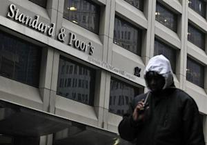 A man walks past the Standard & Poor's building in New York's financial district