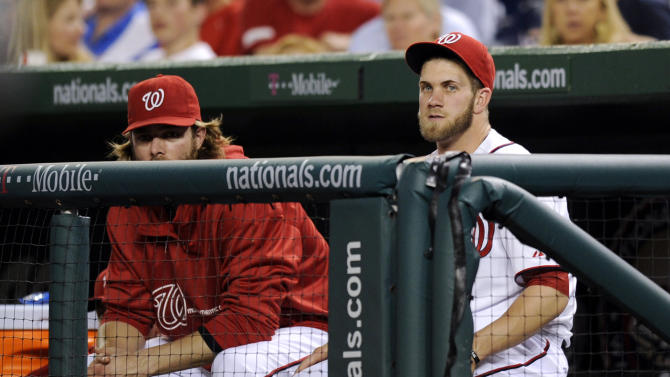 Washington Nationals' Bryce Harper, right, watches from the dugout during the fifth inning of the Nationals baseball game against the Chicago Cubs, Friday, May 10, 2013, in Washington. Harper was not in the starting lineup for the game. (AP Photo/Nick Wass)