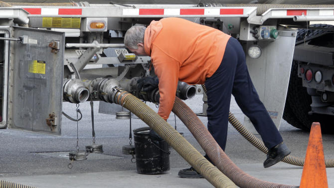 In this Feb. 28, 2012 photo, a delivery driver connects hoses on a gasoline tanker, prior to replenishing the tanks at a BP station in Pittsburgh. The nationwide average for regular unleaded slipped less than a penny to $3.764 per gallon on Tuesday, March 6,2012. That ended a streak of price hikes that began on Feb. 8.  (AP Photo/Gene J. Puskar)