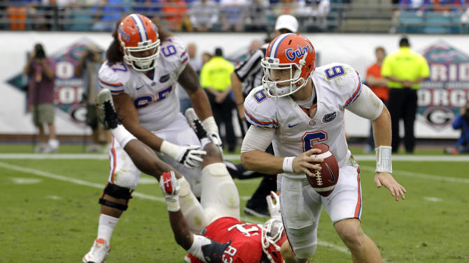 Florida quarterback Jeff Driskel (6) scrambles for yardage after Florida's Jon Halapio (67) blocks Georgia linebacker Cornelius Washington (83) during the first half of an NCAA college football game, Saturday, Oct. 27, 2012, in Jacksonville, Fla. (AP Photo/John Raoux)