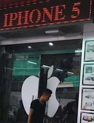 A customer leaves a shop selling Apple products in Hanoi. Apple apologized Friday for its glitch-ridden maps application in the new operating system used by the iPhone 5 and urged customers to use rival programs while improvements are made