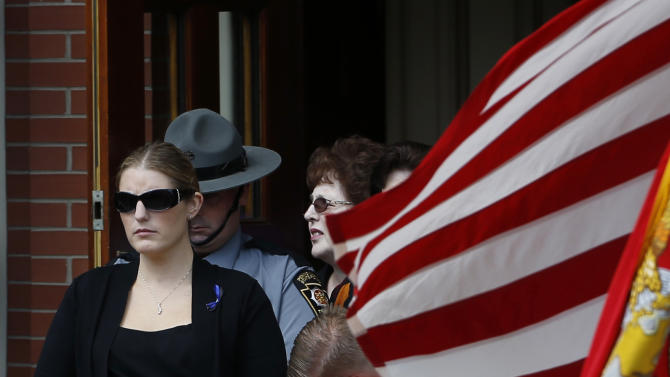 Tiffany Dickson, the widow of Pennsylvania State Trooper Cpl. Bryon Dickson leaves his funeral service Thursday, Sept. 18, 2014, in Scranton, Pa. Dickson was killed on Friday night in an ambush shooting at the state police barracks in Blooming Grove Township. Authorities are looking for 31-year-old Eric Frein, of Canadensis, who has been charged with killing one trooper and wounding another outside the barracks. (AP Photo/Matt Slocum)