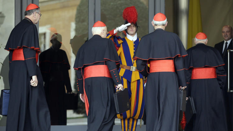 From left, US cardinals Roger Mahoney, Francis George, Donald Wuerl and Theodore McCarrick arrive for a meeting as a Swiss guard salutes them, at the Vatican, Tuesday, March 5, 2013. The Sistine Chapel closed to visitors on Tuesday and construction work got under way to prepare it for the conclave, but five cardinals remained AWOL from the preparatory meetings to discuss who should run the Catholic Church following Benedict XVI's resignation.The Vatican insisted nothing was amiss and that the five cardinals would be arriving in the coming days. (AP Photo/Andrew Medichini)