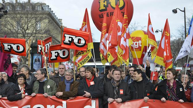 French unions CGT and FO members demonstrate in Paris, Tuesday March 5, 2013, to protest the Socialist government's plans to loosen this country's famously rigid labor rules. Multinationals are shutting factories around France amid Europe's economic slowdown. France's government is trying to stem job losses and turn the stagnant economy around with a new draft labor law being presented at a Cabinet meeting Wednesday. CGT Bernard Thibault, red scarf at center, and FO Jean Claude Mailly, blue scarf, attended the demonstration.(AP Photo/Benjamin Girette)