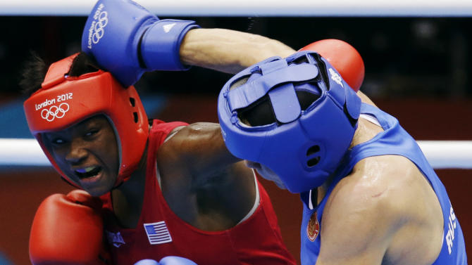 The United States' Claressa Shields, in red, fights Russia's Nadezda Torlopova, in blue, in a women's middleweight 75-kg boxing gold medal match at the 2012 Summer Olympics, Thursday, Aug. 9, 2012, in London. (AP Photo/Patrick Semansky)