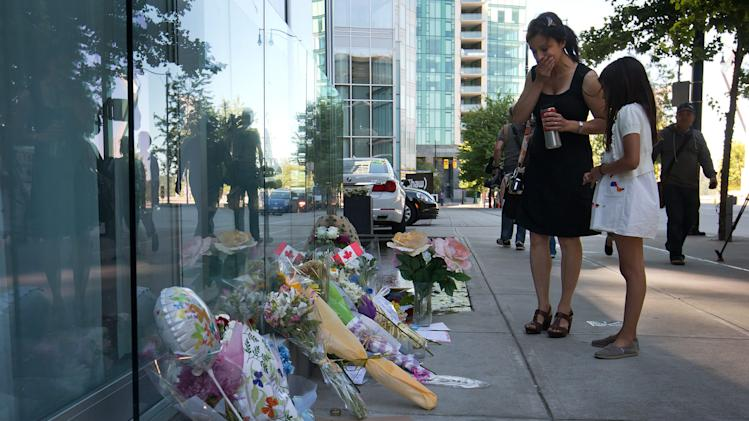 A woman reacts upon finding out Canadian actor Cory Monteith died as she pauses at a memorial for him outside the Fairmont Pacific Rim Hotel in Vancouver, B.C., on Monday July 15, 2013. Monteith's body was found in a room at the hotel Saturday. (AP Photo/The Canadian Press, Darryl Dyck)