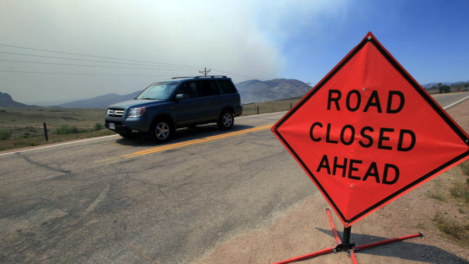 Smoke rises in the background as a motorist drives down Larimer County Highway 74W as a wildfire continues to burn near Livermore, Colo., on Saturday, June 23, 2012. Authorities sent out 992 evacuation notices Friday due to the wildfire burning on more than 100 square miles in northern Colorado as winds pick up. (AP Photo/David Zalubowski)
