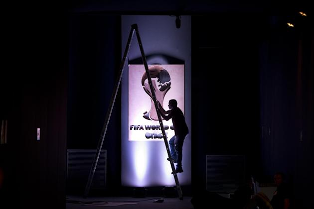 A worker puts the finishing touches to the entrance for the 2014 soccer World Cup draw in Costa do Sauipe, Brazil,  Thursday, Dec. 5, 2013. The draw for the 2014 World Cup finals takes place Friday, D