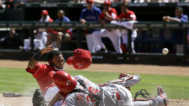 Texas Rangers' Engel Beltre, left, and Cincinnati Reds' Devin Mesoraco, right, collide at the plate as Beltre scores on a bunt by the Rangers' Elvis Andrus in the fifth inning of a baseball game Sunday, June 30, 2013, in Arlington, Texas. (AP Photo/Tony Gutierrez)