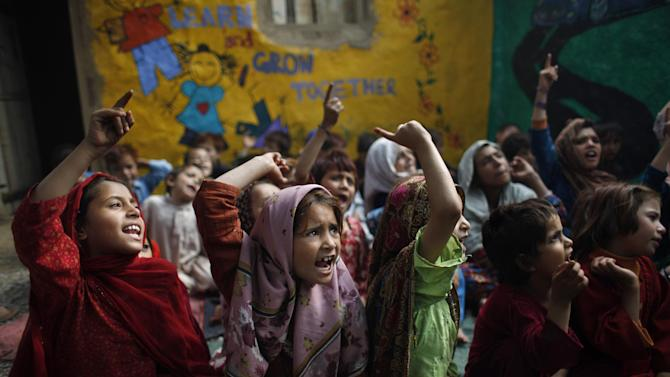Pakistani students, who were displaced with their families from Pakistan's tribal areas due to fighting between militants and the army, chant a song with their teacher, not pictured, during their daily school in a poor neighborhood on the outskirts of Islamabad, Pakistan, Friday, Oct. 19, 2012. A teenage activist recently shot and critically wounded by the Taliban risked her life to attend school, but the threat from the militant group is just one of many obstacles Pakistani girls face in getting an education. Others include rampant poverty, harassment and the government's failure to prioritize education spending. Both sexes have suffered from the lack of funding, but girls, who have lower rates of literacy and school attendance, are in a particularly perilous position. (AP Photo/Nathalie Bardou)