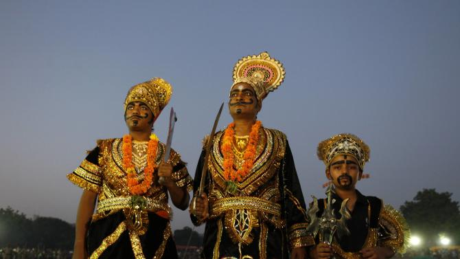 Artists dressed as Ravana, Kumbhkarana and Meghnad pose while standing during Dussehra festival celebrations in Ahmedabad