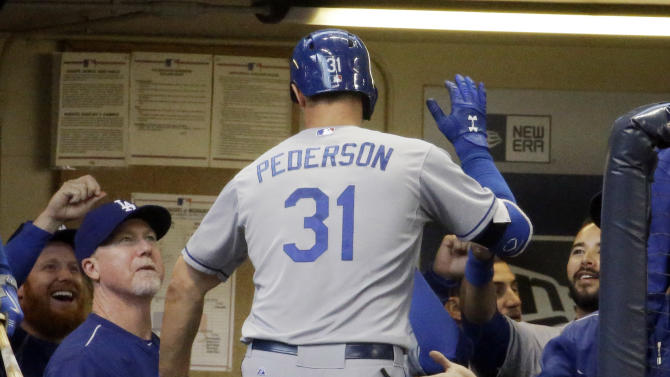 Los Angeles Dodgers' Joc Pederson is congratulated in the dugout after hitting a lead-off home run during the first inning of a baseball game against the Milwaukee Brewers Monday, May 4, 2015, in Milwaukee. (AP Photo/Morry Gash)