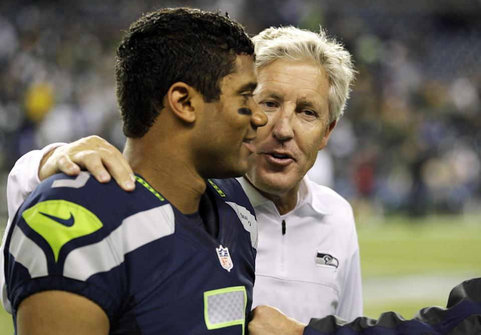 Seattle Seahawks head coach Pete Carroll, right, walks with quarterback Russell Wilson after the Seahawks defeated the Green Bay Packers 14-12 in an NFL football game, Monday, Sept. 24, 2012, in Seattle. (AP Photo/Ted S. Warren)