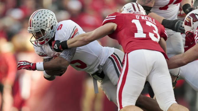 Wisconsin's Conor O'Neill (13) stops Ohio State quarterback Braxton Miller on a run during the first half of an NCAA college football game Saturday, Nov. 17, 2012, in Madison, Wis. (AP Photo/Andy Manis)