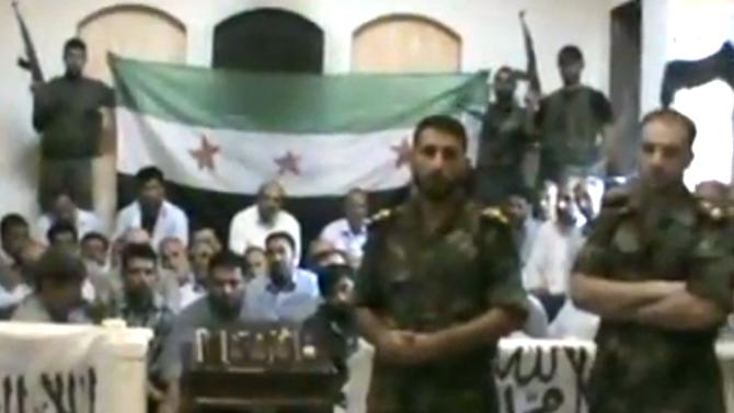 """This image made from a video released by the Baraa Brigades and accessed Sunday, Aug. 5, 2012, purports to show Free Syrian Army soldiers guarding a group of Iranians abducted a day earlier and promising more attacks on Iranian targets in Damascus, Syria. Armed men in the video identify themselves as members of the rebel """"Baraa Brigades"""" and say that at least one of the 48 captives was an officer of Iran's powerful Revolutionary Guards. They claim that Iranians were on a """"reconnaissance mission"""" in the capital Damascus at the time they were abducted. Iran says they are pilgrims who were visiting a shrine. (AP Photo/Baraa Brigades via AP video) THE ASSOCIATED PRESS IS UNABLE TO INDEPENDENTLY VERIFY THE AUTHENTICITY, CONTENT, LOCATION OR DATE OF THIS HANDOUT PHOTO"""
